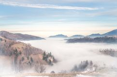 Winter landscape in the mountains. Rural landscape in the evening with fog and clouds on the sky. There are some houses in the image Royalty Free Stock Photography