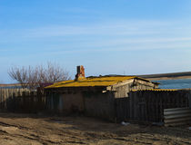 Rural landscape. The evening sun. Small house with a pipe. House on the street near the lake.Astrakhan. Asia royalty free stock photography