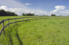 Rural landscape farmland field with wooden fence Stock Image