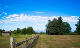 Rural landscape. Rural fence in the green field under blue cloud sky Stock Image