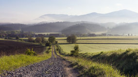 Rural  landscape with fields, mountains and village Royalty Free Stock Image