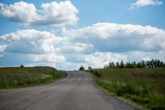 Rural landscape with green field, road and cumulus clouds. In summer Stock Image