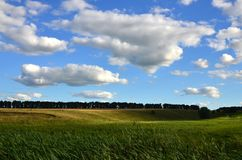 Rural landscape with a green field under a cloudy blue sk. Y Stock Images