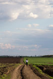 Rural landscape with green fields, soil texture, slops, beautiful sky and girl. Walking Royalty Free Stock Image