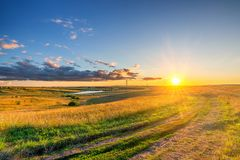 Rural landscape with ground road and wheat field at beautiful summer sunset stock images