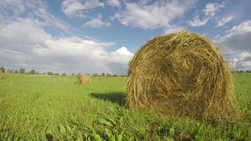 Rural landscape with hay bales on field and rainbow. Timelapse 4K stock video