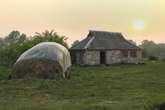 Rural landscape with hay cover against rain awning and stone bui Stock Images