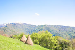 Rural landscape with haystacks in Italian Alps Royalty Free Stock Image