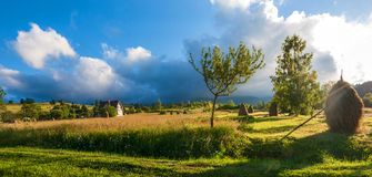 Rural landscape with haystacks in a summer sunny day. Rural mountain landscape with storm clouds. stock image