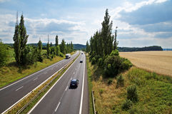 The rural landscape with a highway leading poplar alley, the highway ride three cars and a truck Royalty Free Stock Image