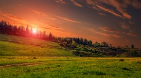 Rural landscape with a hill. Green meadow under sunset, colorful sky with clouds Dramatic morning scene. Beautiful natural landscape stock photography