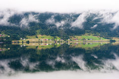 Rural landscape with houses, waterfall and clouds, mirror reflection in the water, Norway Royalty Free Stock Photo