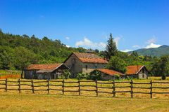 Rural landscape in Maddalena, Italy. Rural landscape with barns and wooden fence in Maddalena, Liguria, Italy with alpine background Royalty Free Stock Photography
