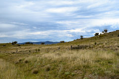Rural landscape with mountains and overcast blue sky Stock Photos