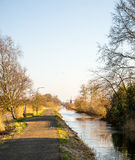Rural landscape. A narrow road and canal leading to a windmill in the distance Royalty Free Stock Image