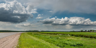 Rural landscape. non urban asphalt road, green meadow, beautiful cloudy sky Stock Photo