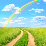 Rural landscape with old road and rainbow Stock Photos
