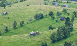 Rural landscape with old wooden houses and green lands in the mountains of Romania Royalty Free Stock Photos