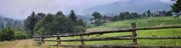 Rural landscape, panorama, banner, with a wooden fence for cattle. The Ukrainian Carpathians royalty free stock images