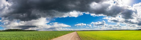 Rural landscape panorama with fields, road and sky. Rural landscape view from field and road. panoramic view of agricultural fields with wheat and rye. panorama stock photography