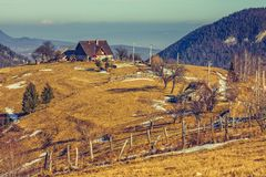 Rural landscape. Peaceful Romanian rural scene with traditional farm and grassland uphill in Moeciu, Brasov county, Trasylvania region, Romania Royalty Free Stock Photography