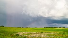Rural landscape, rain clouds and rainbow, time-lapse stock video footage
