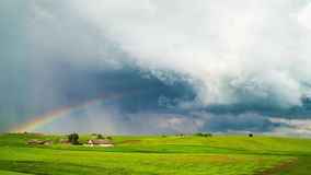 Rural landscape, rain clouds and rainbow, time-lapse stock video