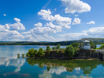 Rural landscape with reflection on a lake. Beautiful landscape with a white structure, green trees and cloudless sky Stock Images