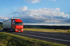 Rural landscape with road and moving red truck Stock Photo