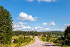 Rural landscape with road. Panorama of the village and the forest. Nature in summer. Big clouds. Rustic panoramic picture. Farming, idyll Stock Image