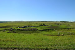 Rural landscape. Siberian Village. Harvested hay rolls. Wooden houses with gardens. Stock Photography