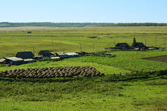 Rural landscape. Siberian Village. Harvested hay rolls. Wooden houses with gardens. Royalty Free Stock Photography