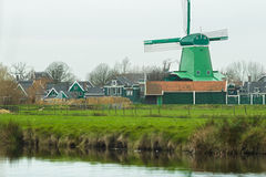 Rural landscape with traditional Dutch windmill and old farm houses on riverbank Royalty Free Stock Photo