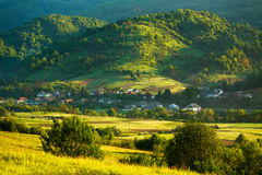 Rural landscape village and fields in mountains at dawn Stock Image
