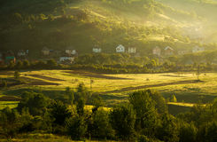 Rural landscape village and fields in mountains at dawn Royalty Free Stock Photo