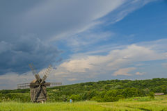 Rural landscape with windmill. Old wooden windmill in museum of folk architecture in Pirogovo, Kiev, Ukraine Stock Photography
