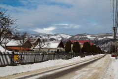 Rural landscape in winter, Romania. Landscape shot with a rural street and some small houses in winter. In background we have the mountains covered by snow Royalty Free Stock Photo