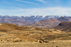 Rural Lesotho Winter Landscape. A winding road passes though the dry winter landscape of rural Leribe in the mountain kingdom of Lesotho royalty free stock photo