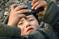 Rural litter boy playing phone games Stock Photos