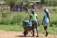 Rural living - village girls carting water home Royalty Free Stock Photo