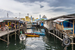 Rural living on wooden stilt houses at fishing port with mosque nearby in Sabah, Malaysia Stock Image