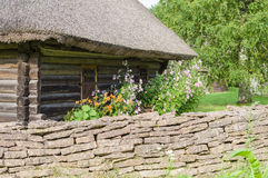 Rural log cabin with garden flowers and limestone fence Royalty Free Stock Photo