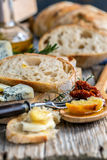Rural lunch with bread, cheese and sun-dried tomatoes. Stock Images