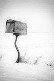 Rural mailbox. Black and white photo of a rural metal mailbox on a crooked post Royalty Free Stock Images