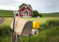 Rural Mailbox. Old-fashioned grey metal mailbox in the country with old red and white schoolhouse in the background surrounded by green grass and fields of royalty free stock photos
