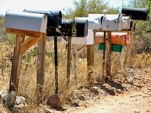 Rural mailboxes. Rural rustic metal mailboxes with dirt road & brush in background Stock Photography