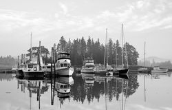 Rural Maine marina. A black and white view of boats anchored at a small rural Maine marina on a quiet, foggy morning Stock Photos