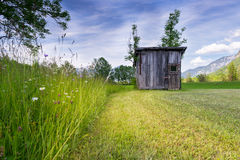 Rural meadow with high grass and old wooden hut. At mowed grass Royalty Free Stock Photography