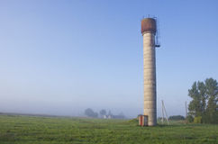Rural morning landscape with water tower and mist fog Stock Image