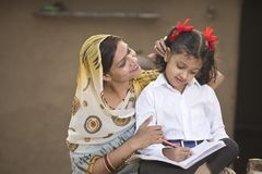 Rural mother helping daughter with her homework stock photo